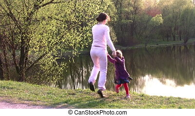 mother with girl on spring pond
