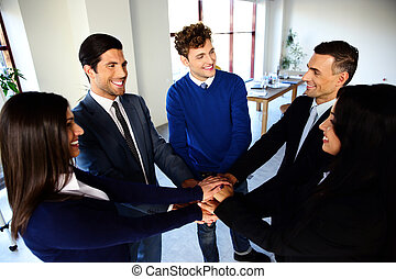 Happy co-workers making pile of hands and looking at each other