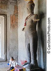 Angkor Wat - Cambodian people sitting for pray with Vishnu...