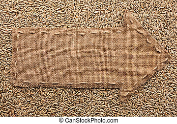 Pointer of burlap with place for your text, lying on a rye...