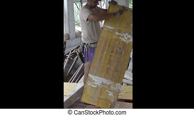 Construction worker removes nails from a wood panel