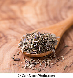 Herbs de Provence. Mixed dried herbs in spoon over wooden...