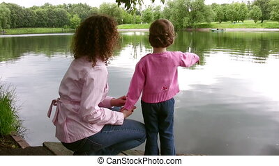 mother with little girl on pond