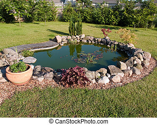 Beautiful classical garden fish pond surounded by grass