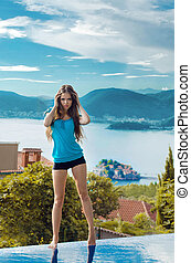 Beautiful girl model posing over a seaside luxury resort in...