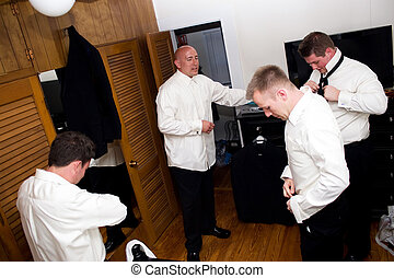 Groomsmen Getting Ready - A groom along with his three...