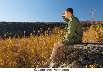 Young Boy Scout on Rock Watching Wide Field - Side View of...