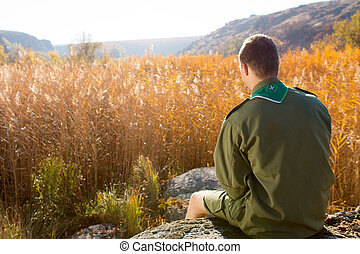 Boy Scout Sitting on the Rock Watching Brown Field - Rear...