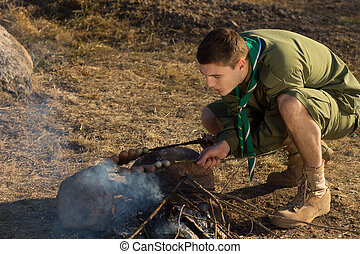 White Boy Scout Making Fire for Cooking at Camp - Young...