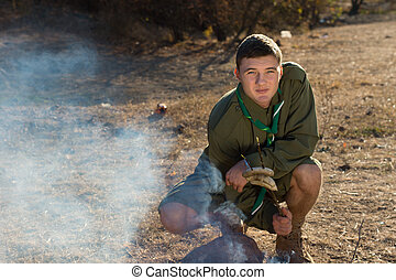 Boy Scout Making Fire on the Campground - Young Boy Scout in...