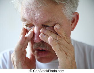 Man has nasal congestion - A senior man tries to relieve his...