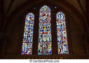 Stained glass church window in reddish tone