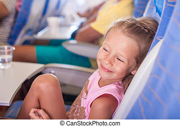 Little smiling happy girl in the aircraft