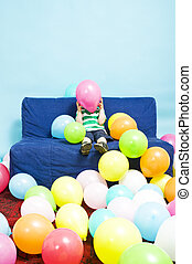 Balloon boy - Young boy sitting on a couch, hiding behind a...