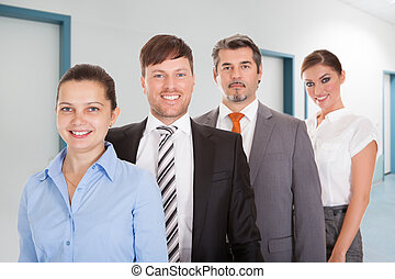 Confident Businesspeople Standing Together In Office