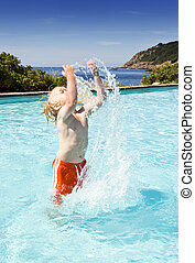 Splashing water - Young boy in an outdoor pool near the sea...