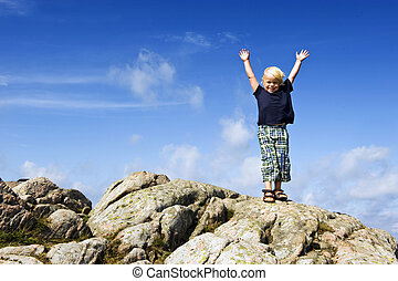 boy reaching top - Young boy with his arms raised in victory...