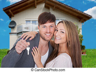 Happy Couple With Key Against New Home