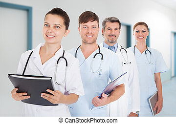 Doctors With Documents And Digital Tablet Standing In Row -...