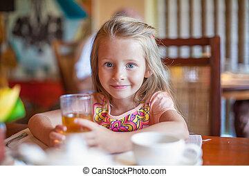 Adorable little girl having breakfast at resort restaurant...