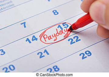 Hand Marking Payday On Calendar - Cropped image of hand...