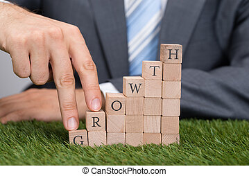 Businessman Climbing Growth Blocks On Grass - Midsection of...