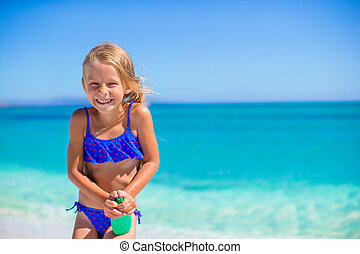 Little happy girl with suntan lotion bottle during beach...