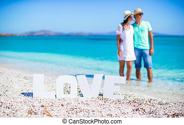 Young happy couple on white beach during summer vacation -...