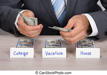 Businessman Saving Cash For College; Vacation And House -...