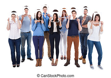 College Students Holding Photographs In Front Of Faces -...