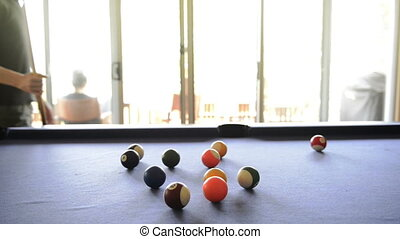 Playing Pool - A man walks behind pool table looking for the...