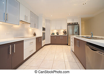 Kitchen 6 - Kitchen with white benches,brown cupboards, and...