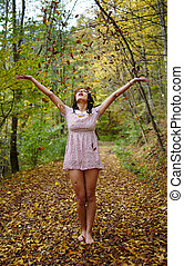 Young woman throwing autumn leaves in the air