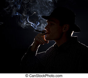 Backlit man smoking a cigar or cigarette with lots of smoke...
