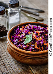 salad with carrots and red cabbage on a dark wood background...