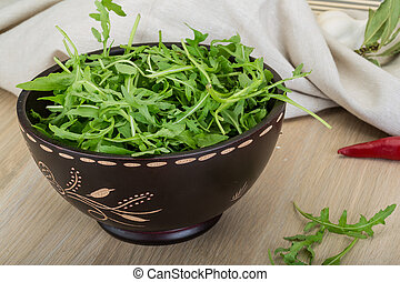 Ruccola leaves mix in the bowl on wooden background