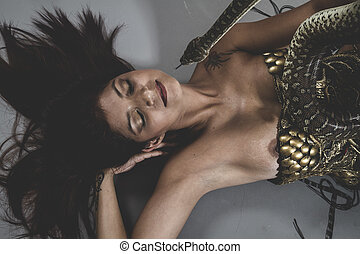 Sexy warrior tattooed woman with big snake and iron corset