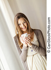 Pretty young woman by the window - Pretty young woman with...