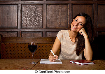 young woman writing with a glass of wine