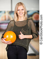 Bowling - Beautiful young woman in a bowling alley is having...