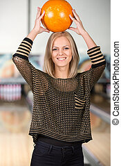 Bowling - Woman in bowling alley A woman is having fun while...