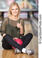 Bowling - Beautiful smiling woman is sitting in a bowling...