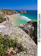 Porthcurno, Cornwall, UK - Sea cliffs over beach in...