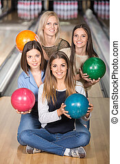 Bowling - Portrait of four happy women in bowling with...