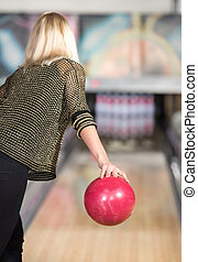 Bowling - Young woman in club for bowling is throwing ball