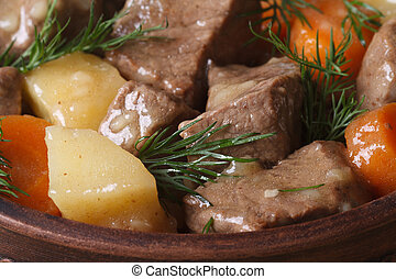 beef stew with vegetables and dill in a pot macro....