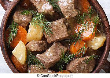 beef stew with vegetables and herbs in a pot macro top view...