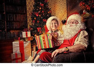 little elf - Happy little boy sitting on the lap of Santa...