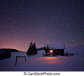 Night landscape - Wooden house with a light in the window....