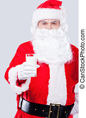 Drink fresh milk Traditional Santa Claus stretching out hand...